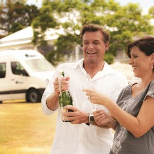 man and woman happily opening a bottle of champagne infrom of a motorhome