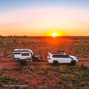 side view of a 4x4 and caravan in dessert with golden sunset background