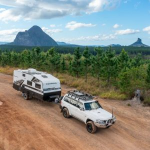 caravan hitched to 4x4 on dirt road with The Glasshouse mountains in the background